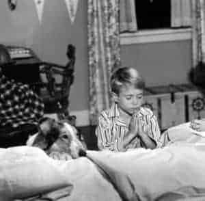 black and white photo of Lassie and Timmy kneeling to say prayers at the bedside