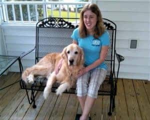 Kolby sitting outside on porch furniture, Sunny lying next to her.