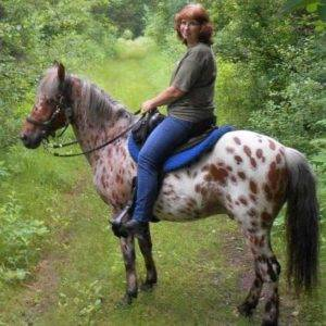 Veleda sitting astride a brown and white spotted horse.
