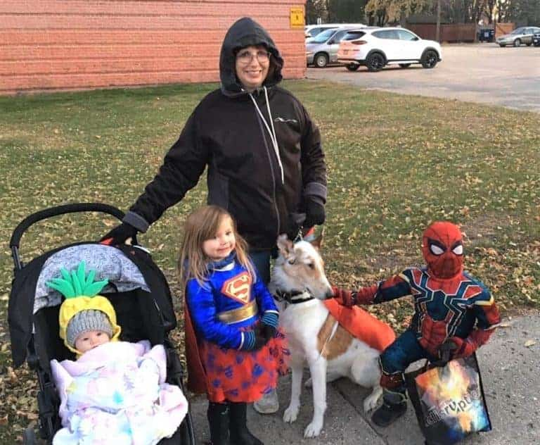 Veleda poses with Tag in Superdog cape/vest, Parker dressed as Spiderman, Lucy as Supergirl, and Ellie wearing a pineapple hat.