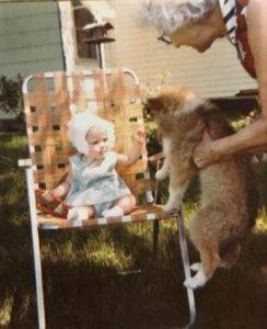 Baby wearing a bonnet and dress sitting in a chair, reaching to pet a puppy being held up to her.
