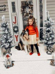 An adorable little girl stands on a holiday-bedecked porch, with her blue merle Collie close at her side.