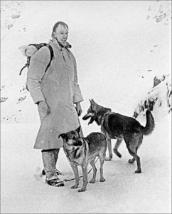 Black and white photo of a tall man in a winter coat standing with 2 search dogs that appear to be German Shepherds