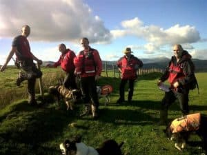 A group of rescue team members and search dogs in a green field
