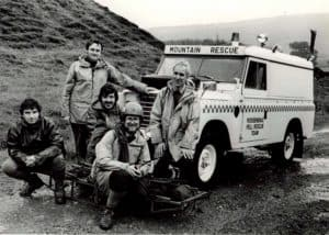 An old black and white photo showing rescue team members standing in front of an emergency vehicle.