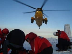 a yellow helicopter hovers above a group of rescue team members