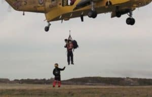 Finn on Stephen's shoulders, midair, being drawn up into a hovering helicopter