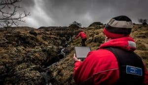 a handler works his dog through a stream-lined gully while an assessor takes notations on an electronic tablet