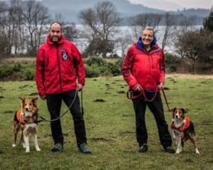 2 uniformed search and rescue dog handlers pose beside their search dogs
