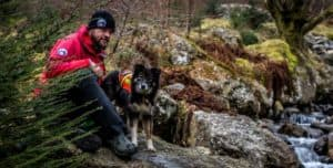 A dog handler kneels near a stream with a mixed breed search dog