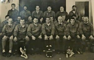 black and white group photo of rescue team, a few with dogs