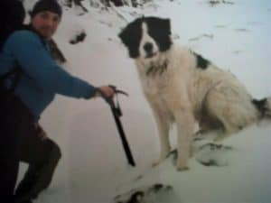 Stephen with a pack and climbing gear on a snowy slope withwith his big Border Collie Roy sitting in the snow beside him