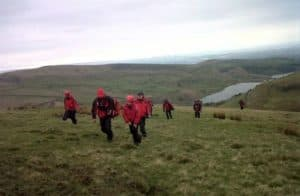 A group of rescuers climb a hill