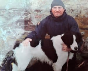 A man in a winter coat and hat poses beside a large black and white Border Collie.