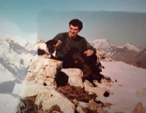 A young Stephen with curly dark hair sits on a snowy hillside with his tricolor Border Collie