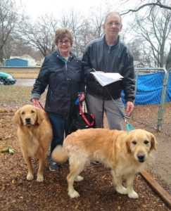 charlie and mary stand with Golden Retrievers Cory and Rascal