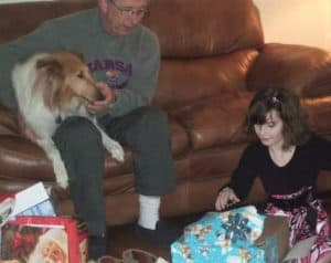 Charlie sits on a couch with Pixie in his lap while Isobel sits on the floor opening presents