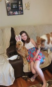 Isobel on the couch between Cory and Pixie. Isobel is hugging Cory, who is wearing bunny ears.