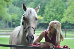 A blonde woman stands beside and smiles adoringly at a palomino horse