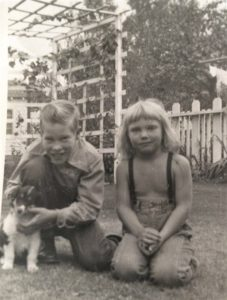 Black and white photo of a small tricolor Collie puppy posing outside with a smiling boy and younger girl wearing suspenders