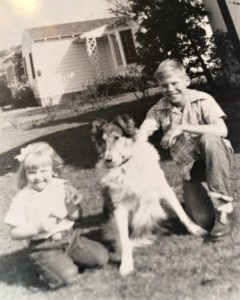 Black and white photo of a Rough Collie sitting outside between 2 kneeling children, one young girl and an older boy