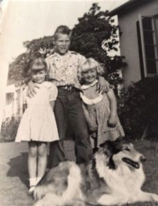 Vintage black and white photo of a sable and white Rough Collie lying at the feet of 3 children, one boy standing with his arms around the shoulders of 2 younger girls