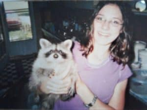 A brown-haired, smiling teenage girl holds a raccoon kit who is reaching for the camera
