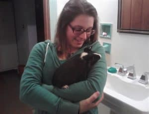 brunette girl holding a black and white guinea pig in her arms