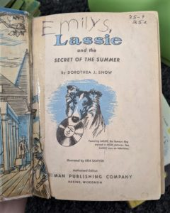 "Title page of a Lassie book clearly showing a ripped preceding page, with childish handwriting spelling ""Emily S."" written it"