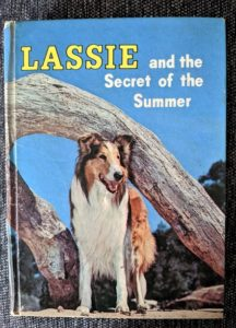 "front cover of a book saying ""Lassie and the Secret of the Summer,"" with a picture of Lassie (a sable and white Rough Collie with a white facial blaze) standing in front of a driftwood tree trunk"
