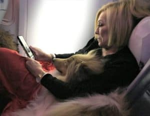 Cody on the plane beside Donna, calmly lying with his head in her lap while she reads