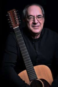 Jeff Hyman poses in a black shirt with his guitar held in front of him