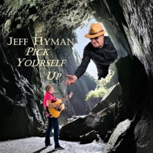 """an album cover reads """"Jeff Hyman - Pick Yourself Up"""" with a picture of Jeff standing in a cave with his guitar and a larger Jeff reaching in through the cave opening with a helping hand to lift him out"""
