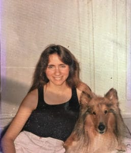 a young woman in a black tank top and skirt poses beside a sable and white Collie, photo from circa 80s-90s