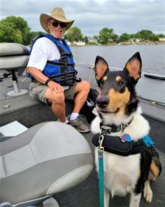 A tricolor Smooth Collie wearing a life vest rides contentedly in a boat next to an older man in a hat
