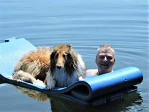 A sable and white Rough Collie lies on a large flotation device while his human pushes him through the lake