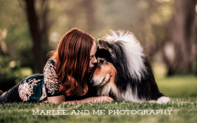 Brianna and Pepsi, a tricolor Rough Collie, lie outside on the grass with their heads together as if they are sharing a secret